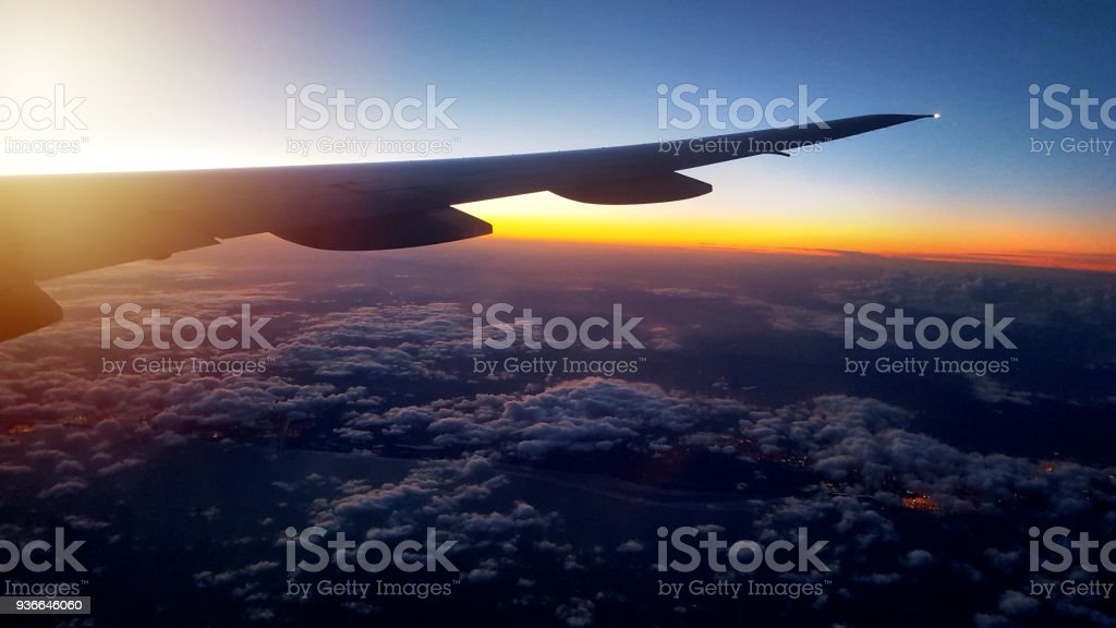 flying above the clouds in sunset stock photo