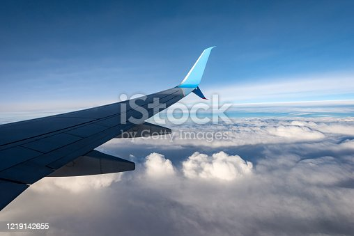 Commercial airplane while flying above the clouds. Aircraft wing view through the window