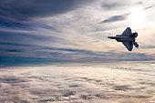 An F22 fighter jet soars above the clouds as the sun begins to set over a beautiful cloudscape.