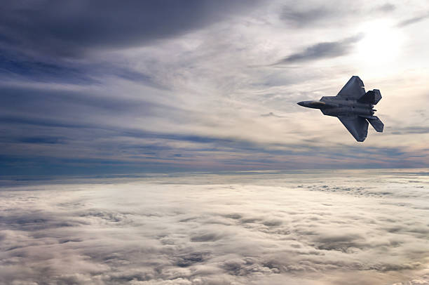 F22 Flying Above the Clouds An F22 fighter jet soars above the clouds as the sun begins to set over a beautiful cloudscape. advanced tactical fighter stock pictures, royalty-free photos & images