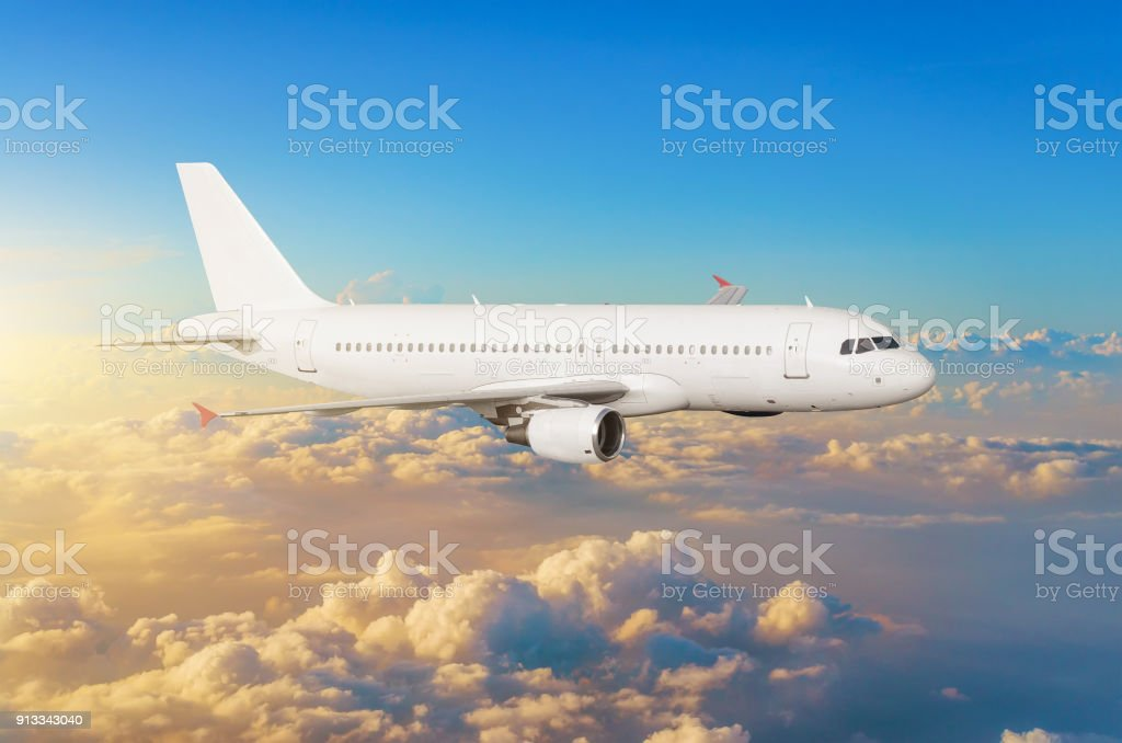 Flying aircraft above the clouds horizon sky with bright sunset colors. stock photo