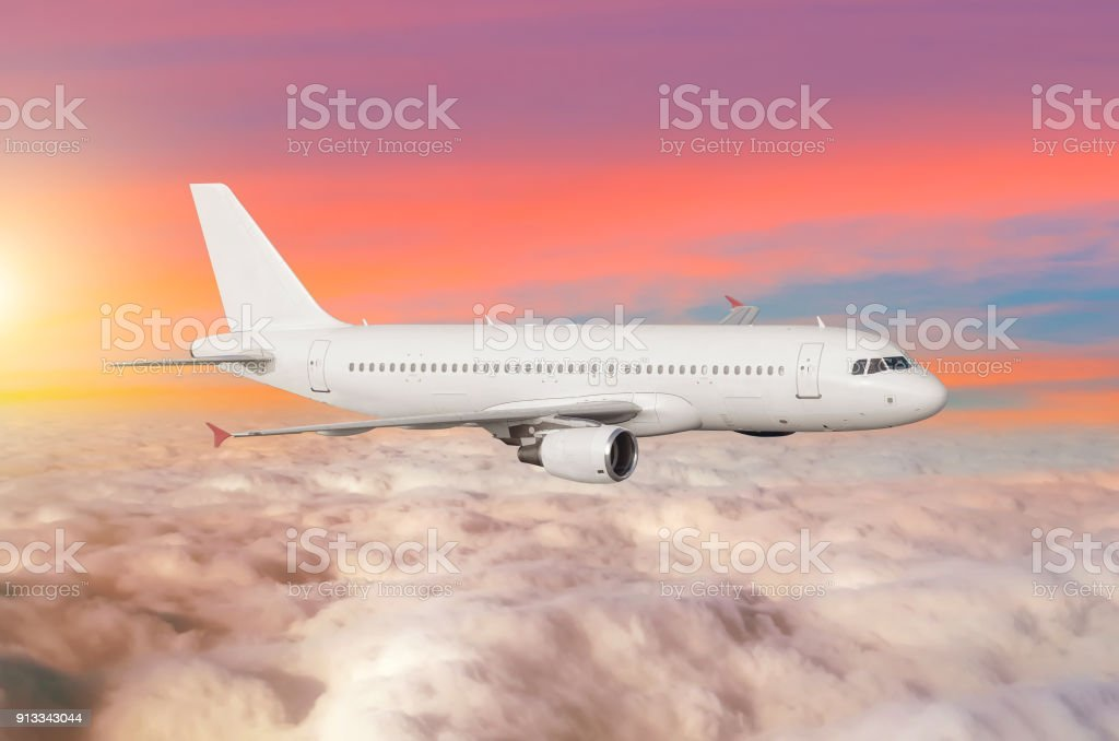 Flying airplane above the clouds horizon sky with bright sunset colors. stock photo