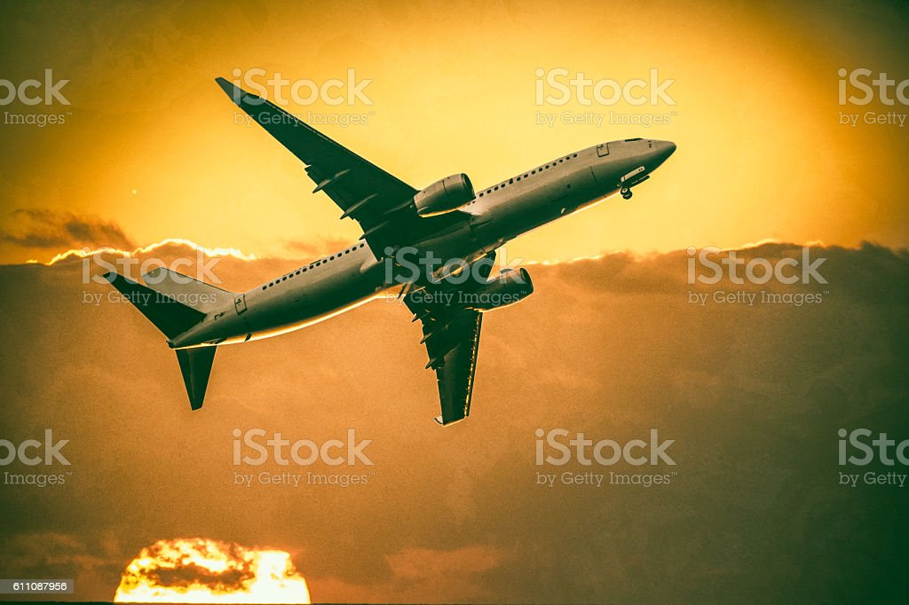 Flying Airplane at sunset stock photo