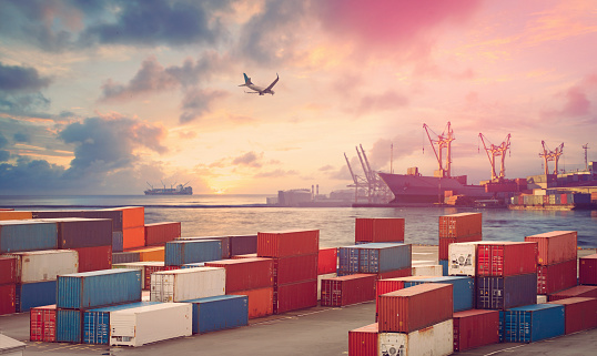 Flying airplane, freight ship, cranes and cargo containers in the harbor in sunset light