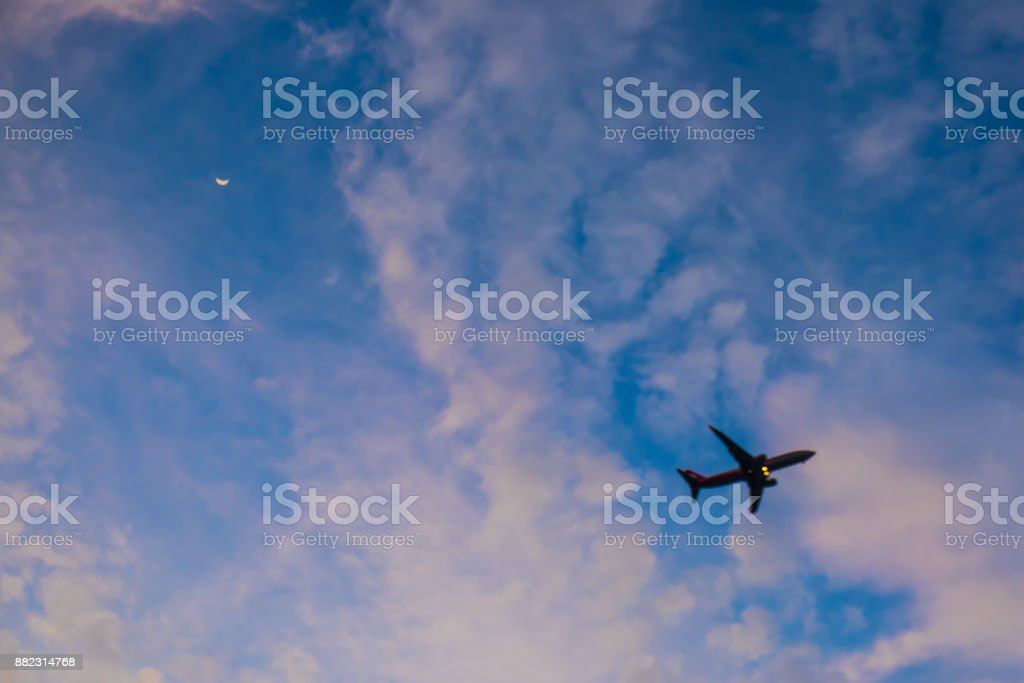 Flying airplane in blue sky with moon