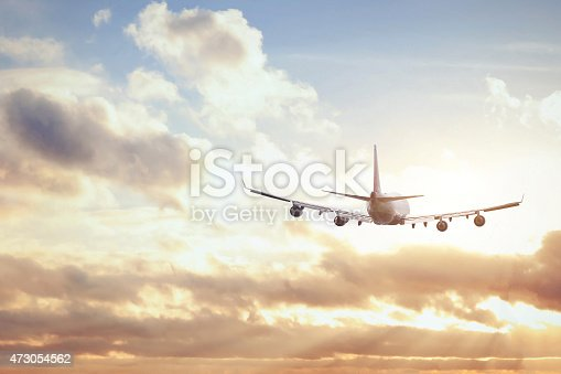 istock Flying airplane in the sky below clouds on a sunny day 473054562
