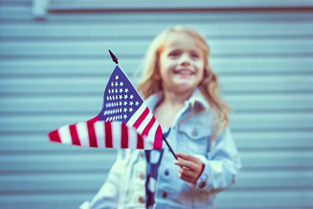 Flying amerikanische Flagge in Mädchen hand.  Geringe Tiefenschärfe auf Flagge – Foto
