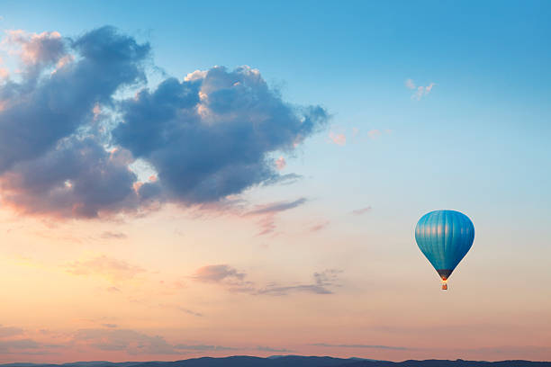ballon volant sur ciel du soir - montgolfière photos et images de collection