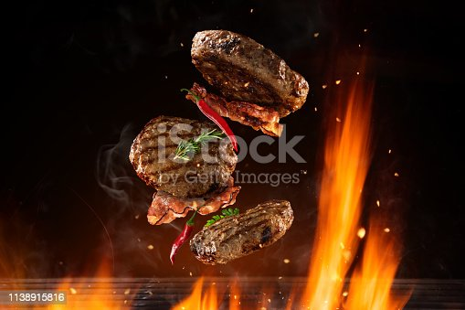 Flying beef hamburgers pieces above burning grill grid, isolated on black background. Barbecue and grill concept