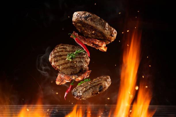 pezzi di hamburger di manzo volanti sopra la griglia in fiamme - hamburger foto e immagini stock