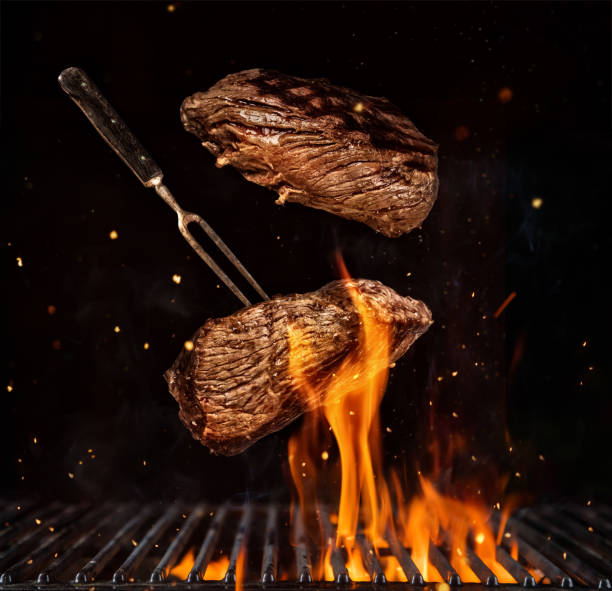 flying beef steaks over grill grid, isolated on black background - meat stock photos and pictures