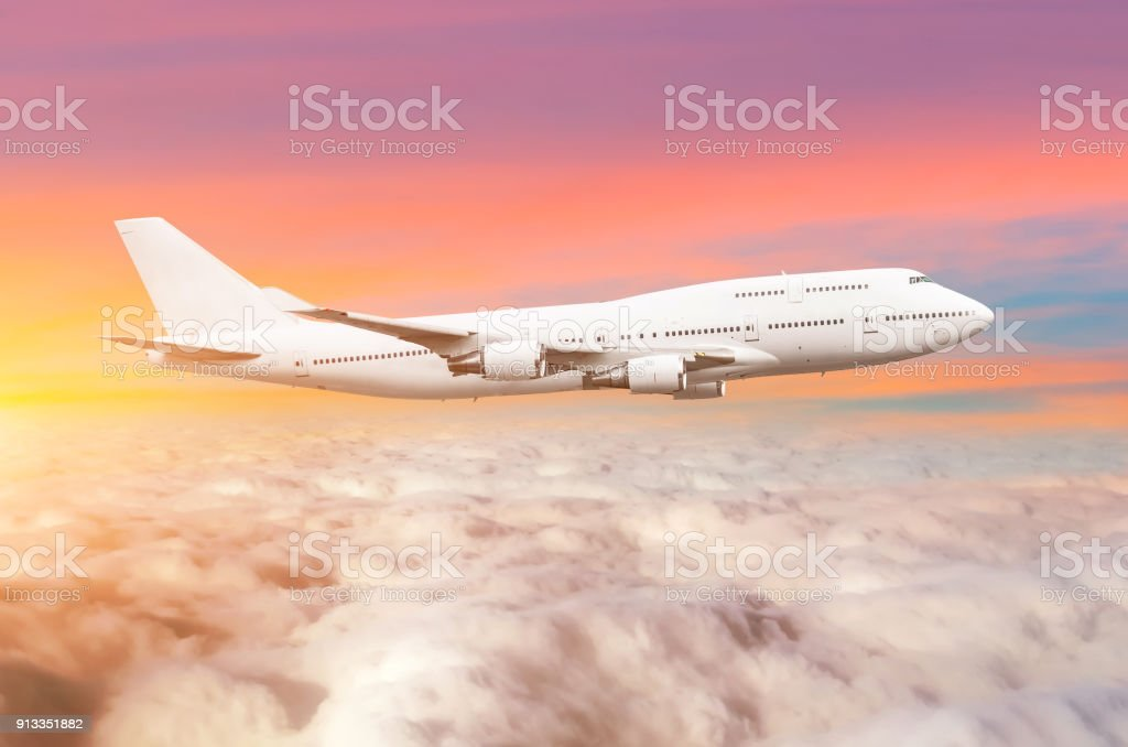 Flying bid double decker airplane above the clouds horizon sky with bright sunset colors. stock photo