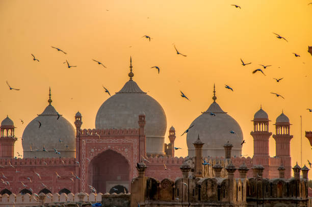 Flying birds over the mosque Fascinating view of Badshahi mosque during sunset. This is biggest mosque in the world lahore pakistan stock pictures, royalty-free photos & images