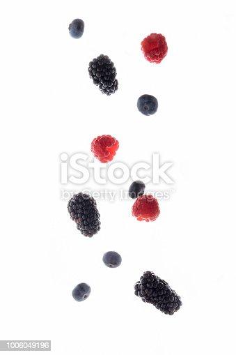 879258868 istock photo Flying blackberry, raspberry and blueberry fruits isolated on white background 1006049196