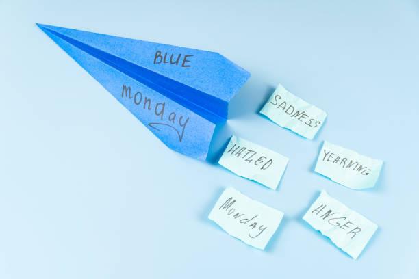 un aereo di carta blu volante con la scritta blue monday contro un cielo blu e lanciando adesivi con le parole. - blue monday foto e immagini stock