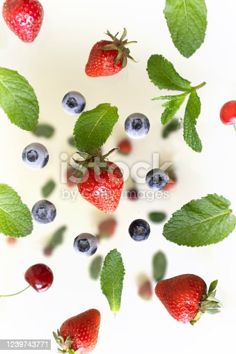 827935944 istock photo flying blueberries forming a circle and strawberries with mint leaves, a drop of bright fruit on a light milk background, 1239743771
