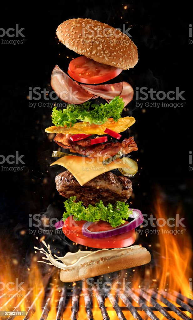 Flying burger ingredients above grill stock photo