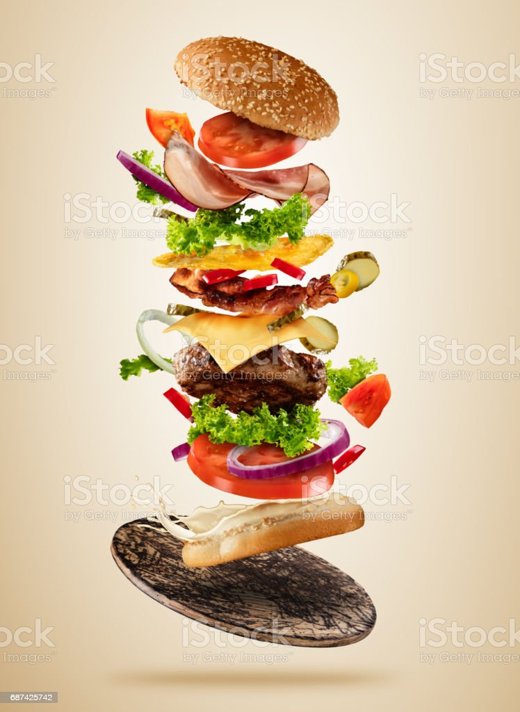 Flying burger ingredients above wooden board on brown background stock photo