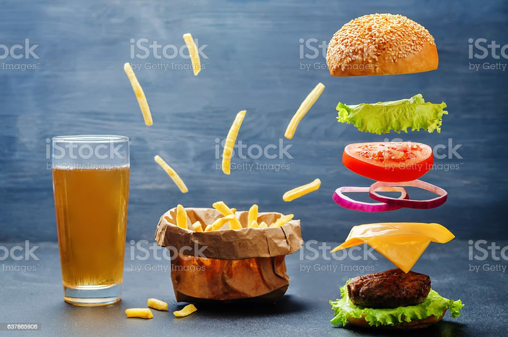 Flying burger with flying French fries and beer stock photo