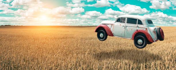 fliegendes auto steigt in den himmel. retro-auto schwebt in der luft über einem goldenen weizenfeld auf dem hintergrund des blauen himmels und malerischen wolken. futuristische ansicht. auto der zukunft. schweben in der luft-auto. - oldtimer veranstaltungen stock-fotos und bilder