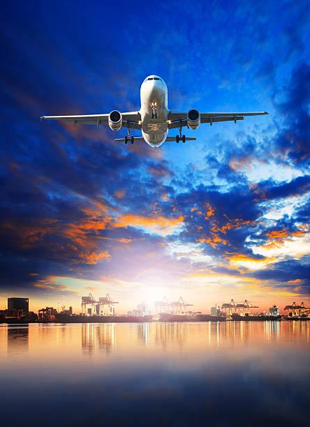 Avión volando sobre el puerto de carga de envío a - foto de stock