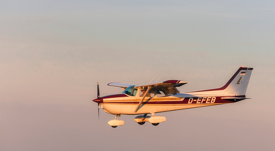 Wesel, Germany - September 9,  2012: Flying Cessna 172 at sunset over Wesel in the Lower Rhine Region of Germany. The Cessna 172 is the most successful aircraft in history. It is a four seat, single engine and high wing aircraft.