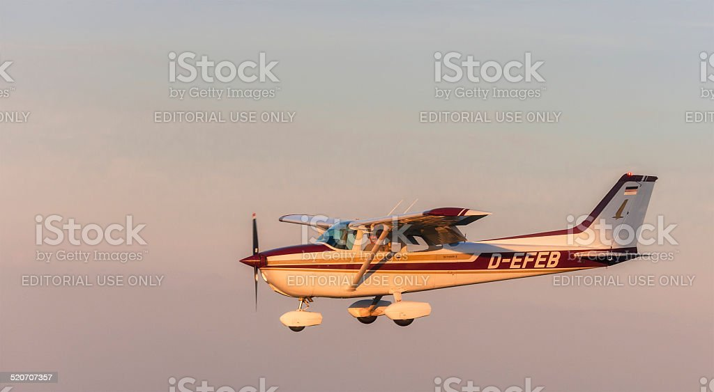 Flying Cessna 172 - Skyhawk  at sunset stock photo