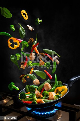 Vegetables and chicken fly through the air into a frying pan