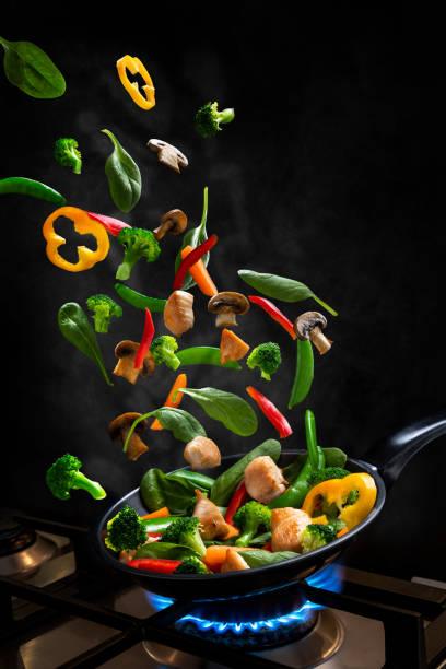 galinha do vôo e frite vegetal do stir, em uma frigideira - stir fry - fotografias e filmes do acervo