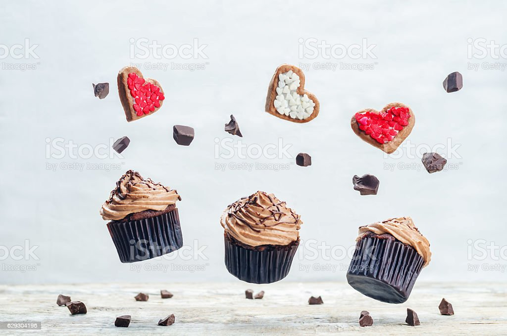 Flying chocolate cupcakes and cookies in the forms of heart stock photo