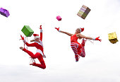 Two young girls wearing Santa hats show their happy  feelings for Christmas with jumping up in mid air,  performing gymnastic poses. Christmas presents fly all around them from every angle.
