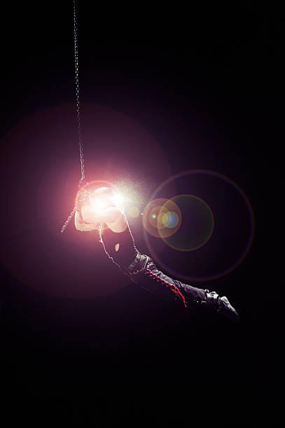 flying zirkus künstler in hellen spotlight - trapez stock-fotos und bilder