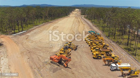 istock AERIAL: Flying close above gravel roadwork zone and construction machinery 1186505862