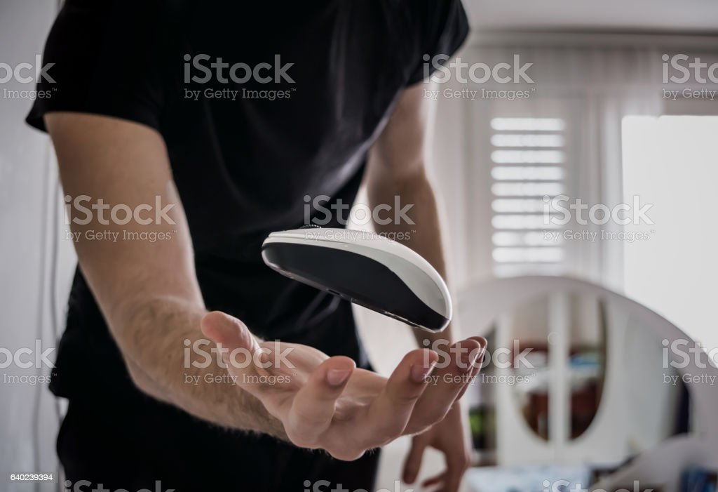 Flying computer mouse (Guy trowing computer mouse in the air) stock photo