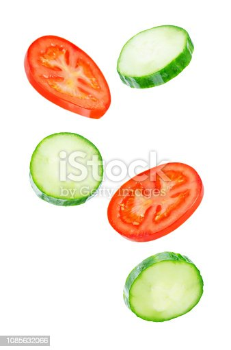 Flying Cucumber slices with tomato slices on a white background. tinting. selective focus