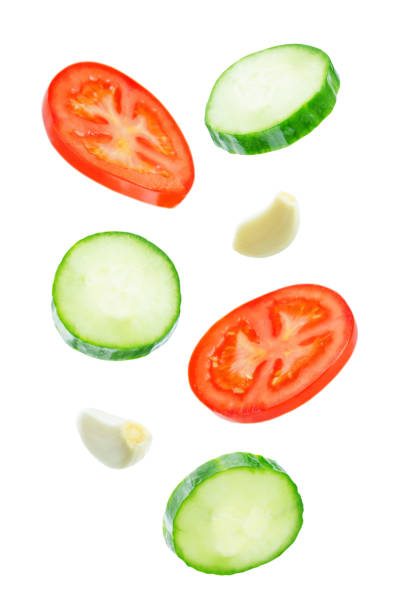 Flying Cucumber slices with tomato slices stock photo
