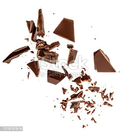 istock Flying Dark chocolate pieces isolated on white background.  Chocolate bar chunks, shavings and cocoa crumbs Top view. Flat lay 1219757819