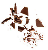 Flying Dark chocolate pieces isolated on white background.  Chocolate bar chunks, shavings and cocoa crumbs Top view. Flat lay