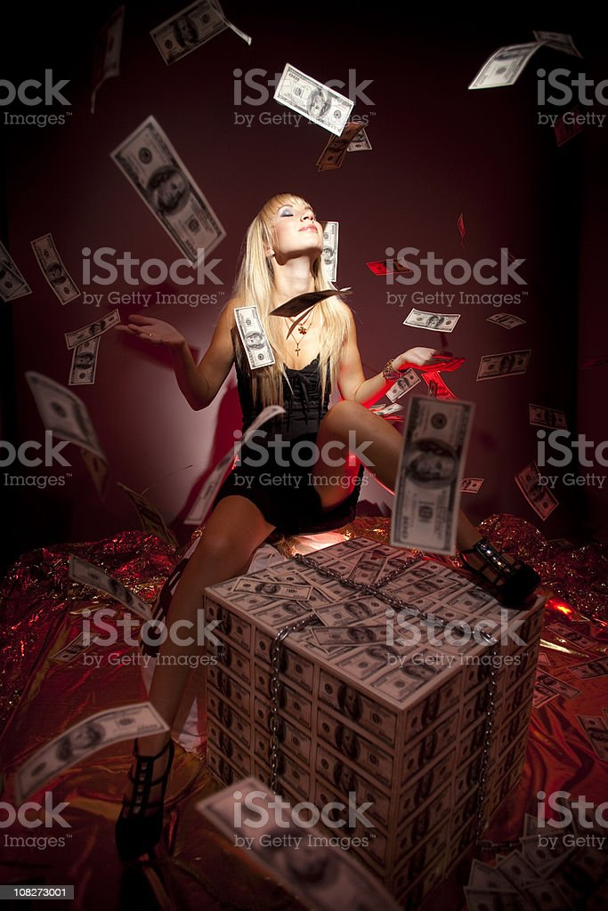 Flying dollars on beautiful blonde rich young woman royalty-free stock photo