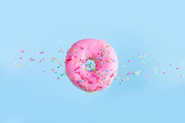 flying doughnuts on blue - posypka zdjęcia i obrazy z banku zdjęć