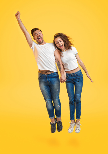 Flying excited man and woman on yellow background