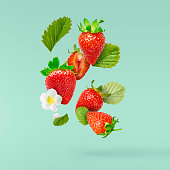 Flying Fresh tasty ripe strawberry with green leaves