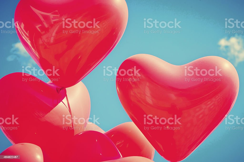 Flying heart shaped balloons in a clear sky stock photo