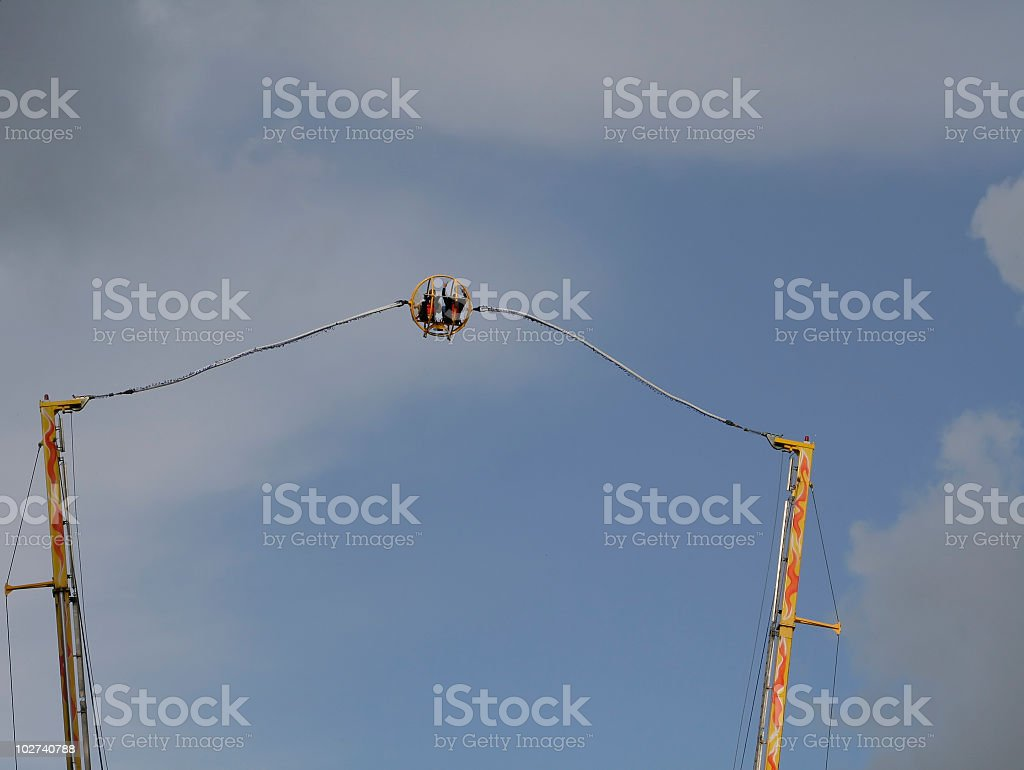Flying high in cloudy sky, human slingshot stock photo