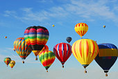 Colorful hot air balloons flying high in the sky at a Balloon Festival in the fall near Albuquerque, New Mexico.