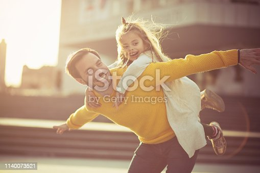 Flying high with my daddy. Father and daughter playing in the city street.