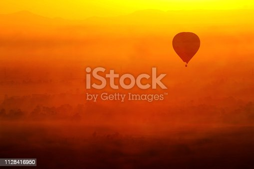 Hot air balloon flying in Luxor, Egypt. In a beautiful sunrise with foggy orange background.
