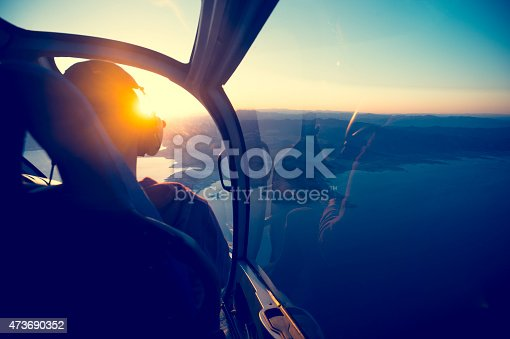 Flying in a helicopter over lake mead in Arizona. View is from behind with a view of  lake mead near the grand canyon. Time of ay is sunset or sunrise with a beautiful view and blue sky. Copy space on right. Can be flipped.