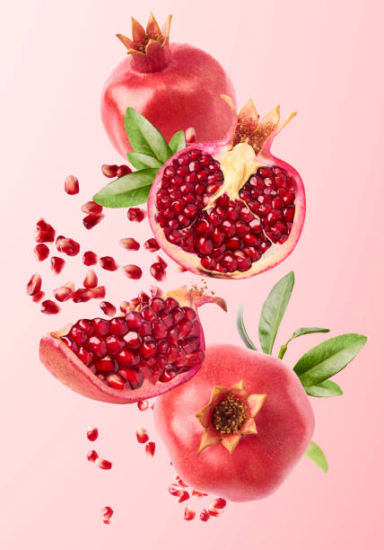 flying in air fresh ripe whole and cut pomegranate with seeds and leaves - romã imagens e fotografias de stock