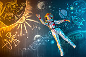Cheerful girl astronaut flying free in outer space. The illusion of flight on a background of the space drawing in chalk